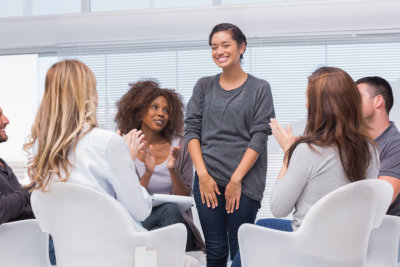 patient in group therapy while others are clapping her