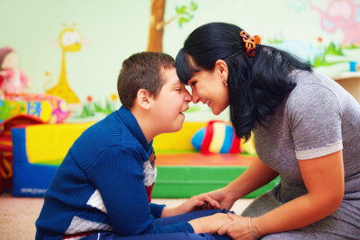 portrait of mother and her beloved son with disability in rehabilitation center