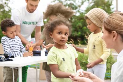 volunteers giving vitamin tablets to poor children